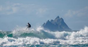 SURF'S UP: A surfer rides the waves under the shadow of the Skellig Islands in Ballinskelligs, Co Kerry. Photograph: Stephen Kelleghan