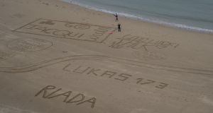 Good-luck messages are written on the beach before the Wales Ironman race.
