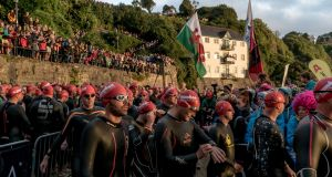 Competitors line up before dawn on the beach in Tenby, Wales, before the start of the Wales Ironman earlier this month. Photograph: Andrew Testa/The New York Times
