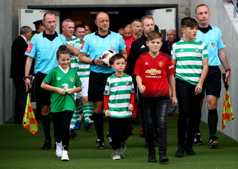 LEADING OUT: Liam Miller's children Belle, Leo and Kory and his nephew Tom (second from left) lead the teams out at the late soccer player's tribute match in Páirc Uí Chaoimh Photograph: James Crombie/INPHO