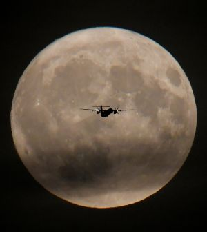 FLY ME TO THE MOON: A passenger plane is seen with the full moon behind as it begins its final landing approach to Heathrow Airport in London, Britain on September 24th, 2018. Photograph: Toby Melville/Reuters