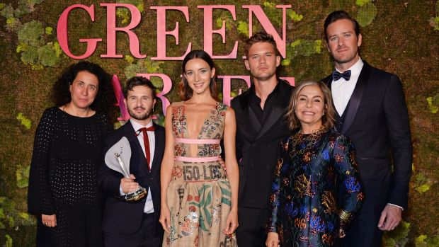 Sara Maino, Gilberto Calzolari, winner of the Franca Sozzani GCC Award for Best Emerging Designer, a model wearing the winning design, Jeremy Irvine, Desiree Bollier, chair Value Retail and Armie Hammer pose backstage at The Green Carpet Fashion Awards in Milan, Italy. Photograph: Dave Benett