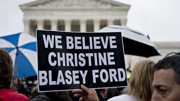 "A demonstrator holds a ""We Believe Christine Blasey Ford"" sign outside the US supreme court in Washington on Monday. Photograph: Andrew Harrer/Bloomberg"