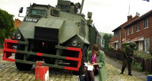A journalist works on her story in front of an armoured car on the Ardonne Road at the Catholic and Protestant divide  in Belfast in  2001.  Photograph: Adrian Dennis/AFP/Getty