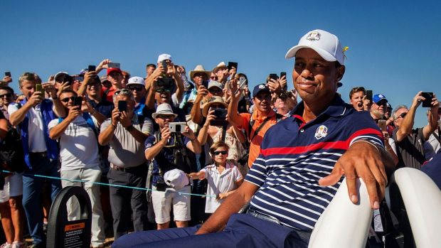 Fans watch on as Tiger Woods passes by in a buggy. Photo: Oisin Keniry/Inpho