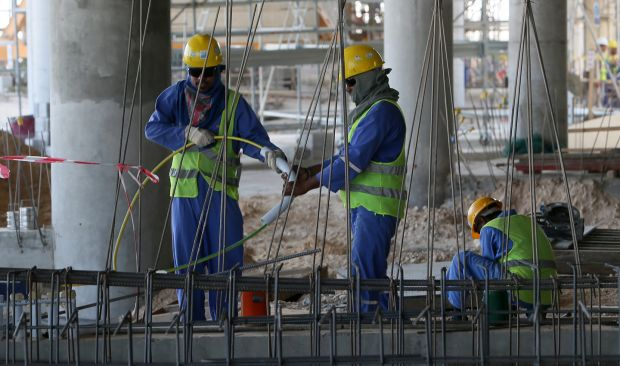 Migrant labourers work on a construction site in Doha in 2013. Photograph: Karim Jaafar/AFP/Getty Images)