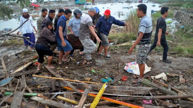 Residents carry the body of a tsunami victim in Palu, Central Sulawesi, Indonesia, Saturday. Photograph: AP