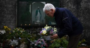 Peter Mulryan, a survivor of the Tuam mother and baby home,   lays flowers  at the site  where the bodies of 796 babies were uncovered. Photograph: Reuters/Clodagh Kilcoyne