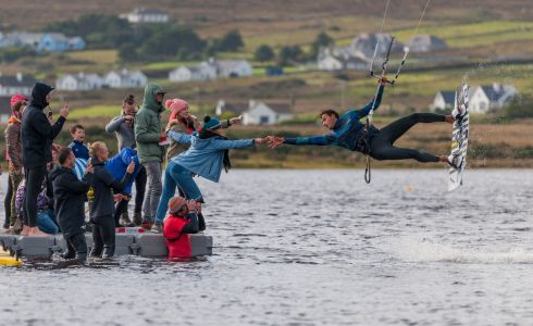 GRABBING A SLICE: Pro kitesurfer Maxime Camus from France, drops in for some take away pizza at the Achill Island Battle for the Lake kite surfing competition. Photograph: Michael Mc Laughlin