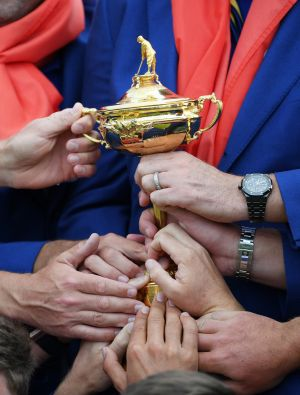 HANDS ON: Members of Team Europe all hold The Ryder Cup trophy as they celebrate after winning The Ryder Cup during singles matches of the 2018 Ryder Cup at Le Golf National on September 30th, 2018 in Paris, France. Photograph: Ross Kinnaird/Getty