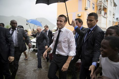 CAUGHT IN THE RAIN: French President Emmanuel Macron visits Quartier d'Orleans, during a trip in the French West Indies, one year after Hurricanes Irma and Maria damaged the French Caribbean island of Saint-Martin. Photograph: Thomas Samson/Reuters