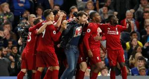 Sturridge celebrates his goal with team mates and a rogue fan. Photo: John Sibley/Reuters