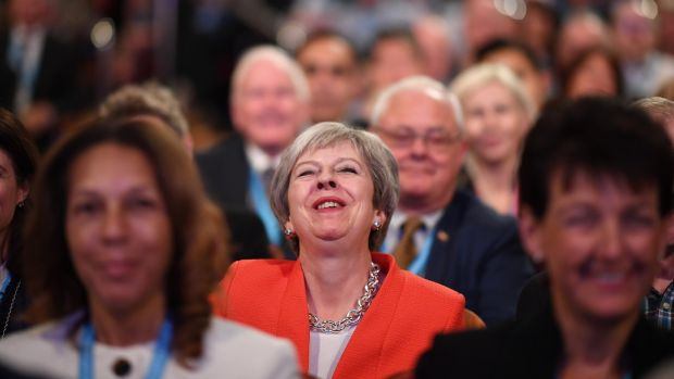 UK prime minister Theresa May laughs as she sits in the audience during the annual Conservative Party conference. Photograph: Jeff J Mitchell/Getty Images