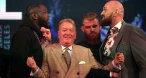 Deontay Wilder (left) and Tyson Fury (right) react as promoter Frank Warren (centre) keeps them apart during a press conference at BT Sport Studio, London. Photo: Steve Paston/PA Wire