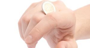 Twisting two euro coin with the knuckles, close-up composition isolated over the white background