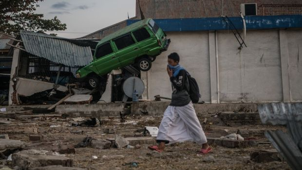 A man walks past a car wedged into a building by the tsunami in Palu, Indonesia. Photograph: Carl Court/Getty Images
