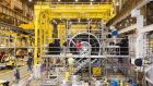 Workers install scaffolding around a gas turbine at a General Electric factory in Greenville, South Carolina.
