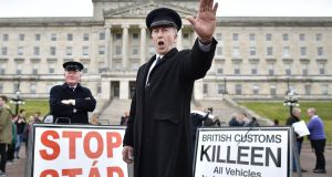 Two men dressed as customs officers protesting  outside Stormont against Brexit. There is a solution which protects the open Border, and the jobs that go with it, without adding to regulatory checks across the Irish Sea. Photograph:  Getty Images