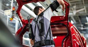"Recent trials of upper-body ""exoskeletons"" by production line staff show that lightweight wearable frames greatly reduce the physical strain of repetitive overhead assembly work."