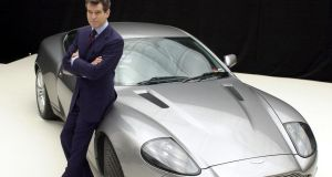 Pierce Brosnan as James Bond in 2002 next to an Aston Martin V12 Vanquish, as seen in Die Another Day. File photograph: PA Wire.