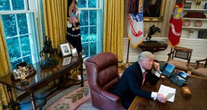 President Donald Trump speaks on the phone in the Oval Office of the White House, with a photo of his father, Fred Trump, behind him. Photograph: Doug Mills/The New York Times