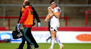 Ulster's John Cooney departs the action at Thomond Park having suffered a head injury against Munster. Photograph: Ryan Byrne/Inpho