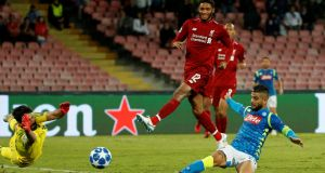 Napoli's Lorenzo Insigne scores his side's winning goal past Liverpool goalkeeper Alisson during the  Champions League Group C match at  Stadio San Paolo. Photograph: Ciro De Luca/Reuters