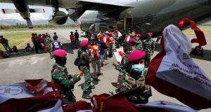 Soldiers unload food aid from a Singapore Armed Forces (SAF) supply plane at Mutiara Sis Al-Jufri Airport in Palu, Indonesia. Photograph: Darren Whiteside/Reuters