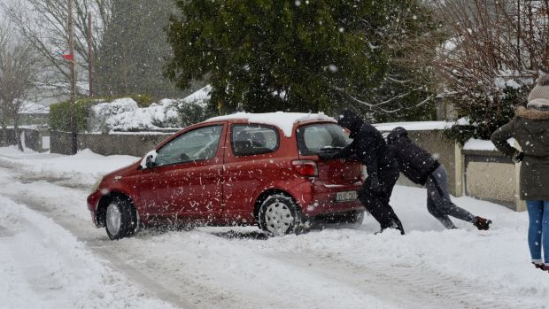A file image from March of this year of people trying to push a car through snow in Dunboyne Co Meath. Photograph: Alan Betson/The Irish Times