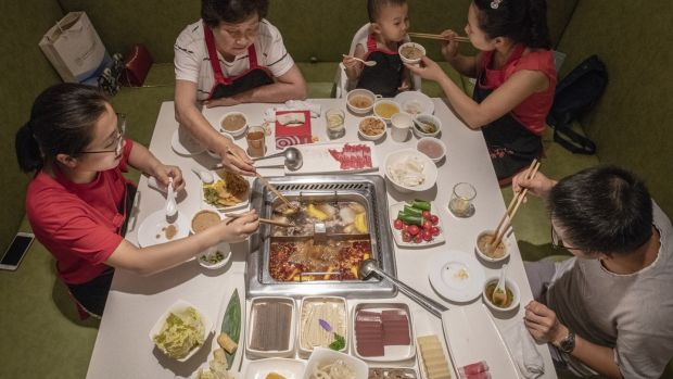 Diners at a Haidilao restaurant: hot pot, in which diners cook their own meat and vegetables in a boiling broth, is a favourite meal in China. Photograph: Gilles Sabrié/ The New York Times