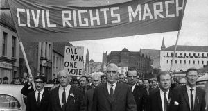 The Derry Civil Rights march moving off from Waterside railway station, heading towards Duke street. Leading the marchers are  Eddie McAteer, the Nationalist leader,  Gerry Fitt, Republican Labour MP, and  Ivan Cooper, chairman of the Derry branch of the Labour Party.