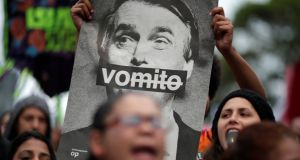 A demonstrator shows a picture of Brazilian presidential candidate Jair Bolsonaro, that reads: 'vomit' during a protest against him in São Paulo, Brazil. Photograph: REUTERS/Ueslei Marcelino