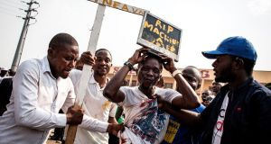 "Opposition supporters carry a cross and computer screen with the words ""RIP voting machine"" on it, during a rally. Photograph: John Wessels/AFP/Getty Images"