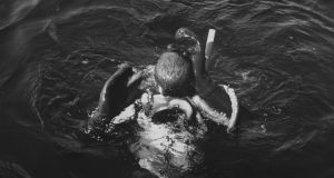 A diver surfaces with an octopus after an underwater wrestling match. Photo: Peter Stackpole/The LIFE Images Collection/Getty Images