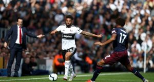 Fulham's Cyrus Christie plays a pass around Arsenal's Alex Iwobi during the Premier League match at Craven Cottage, London. Photo: John Walton/PA Wire