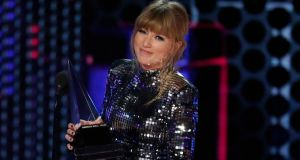 Taylor Swift accepts Artist of the Year at the American Music Awards in Los Angles. Photograph: Mario Anzuoni/Reuters