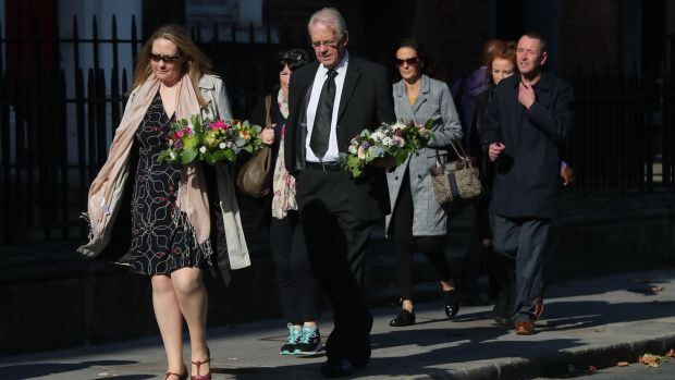 Mourners carry floral tributes to the Pro-Cathedral in Dublin on Wednesday. Photograph: Niall Carson/PA Wire