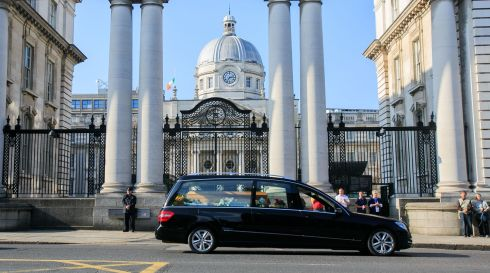 The remains of Emma Mhic Mhathúna pass Government Buildings on Merrion Street, Dublin, following her funeral Mass. Photograph: Gareth Chaney Collins