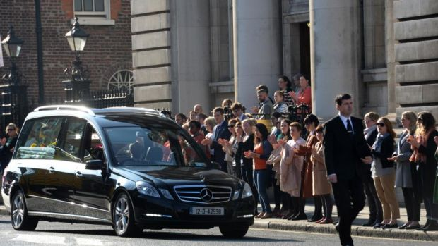 Department of Finance staff applaud as the funeral cortege passes Government Buildings. Photograph: Dara Mac Dónaill