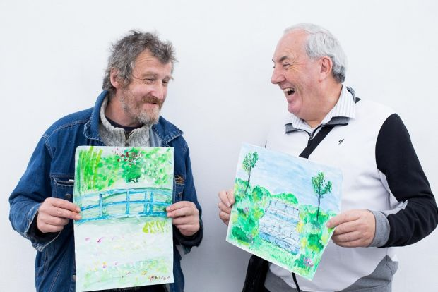 Donal Moran and John Adam with their paintings.