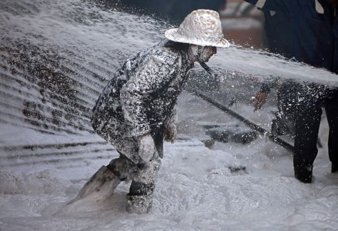 A firefighter is covered with Aqueous Film Forming Foam as he tries to control a fire that erupted in a thinner manufacturing plant on the outskirts of Ahmedabad, India. Photograph: Amit Dave