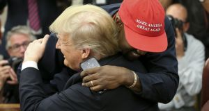 US president Donald Trump hugs rapper Kanye West at the White House where they spoke of prison reform. Photograph: Oliver Contreras
