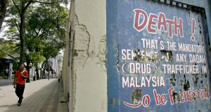 A pedestrian  walks past a wall carrying a message highlighting Malaysia's mandatory death penalty for drug trafficking in Kuala Lumpur. Photograph:   Tengku Bahar/AFP/Getty Images