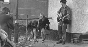 Two young women negotiate a barricade next to an armed soldier on the Falls Road, Belfast in 1969. Photograph:  Evening Standard/Getty Images