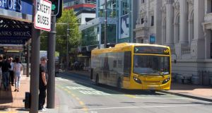 A yellow bus travels down Manners Street in downtown Wellington, New Zealand. Photograph: Smith Collection/Gado/Getty Images