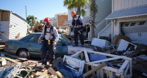 Search and rescue workers walk amidst the destruction left by Hurricane Michael in Mexico Beach. Photograph: The New York Times