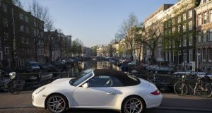 A white Porsche AG automobile sits parked on a bridge over a canal in Amsterdam, Netherlands.
