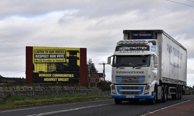 NEWRY, NORTHERN IRELAND - OCTOBER 09: A lorry crosses the border past a Border Communities Against Brexit billboard on October 9, 2018 in Newry, Northern Ireland. Talks on the Irish border are thought to be at a crucial stage as the EU and the UK attempt to resolve their differences over the backstop plan to avoid a hard border between the Republic of Ireland and Northern Ireland which is part of the United Kingdom. EU officials had expressed optimism at the weekend regards a Brexit deal being struck by the end of the year. (Photo by Charles McQuillan/Getty Images)