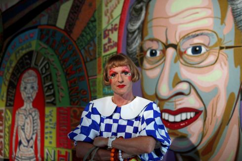"ALTER EGO: British artist Grayson Perry, dressed as ""Claire"", his female alter-ego, poses in front of his art work ""Comfort Blanket, 2014"" during a press visit of his exhibition ""Vanity, Identity, Sexuality"" at the Monnaie de Paris in Paris, France on October 16th, 2018. Philippe Wojazer/Reuters"