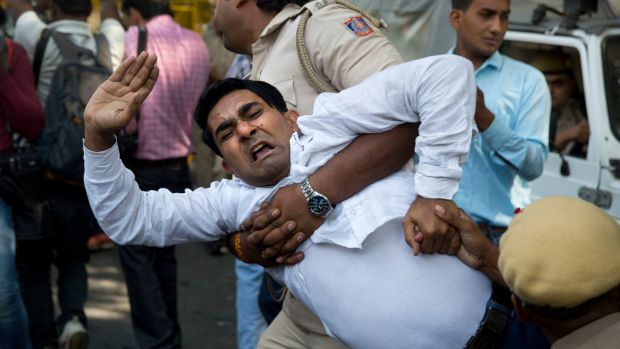 An Indian policeman takes away a Congress party worker during a protest against Akbar in New Delhi. Photograph: Manish Swarup/AP Photo